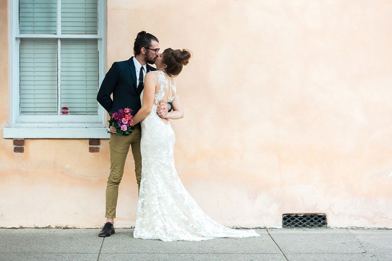 French_Boho-bride_and_groom_kissing_peach_backdrop