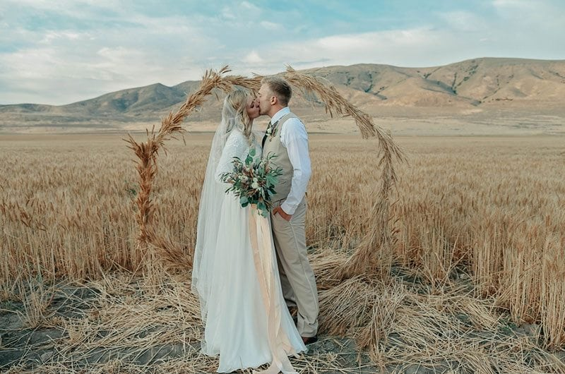 Bountiful Wheat Harvest Bride And Groom Kissing In Field