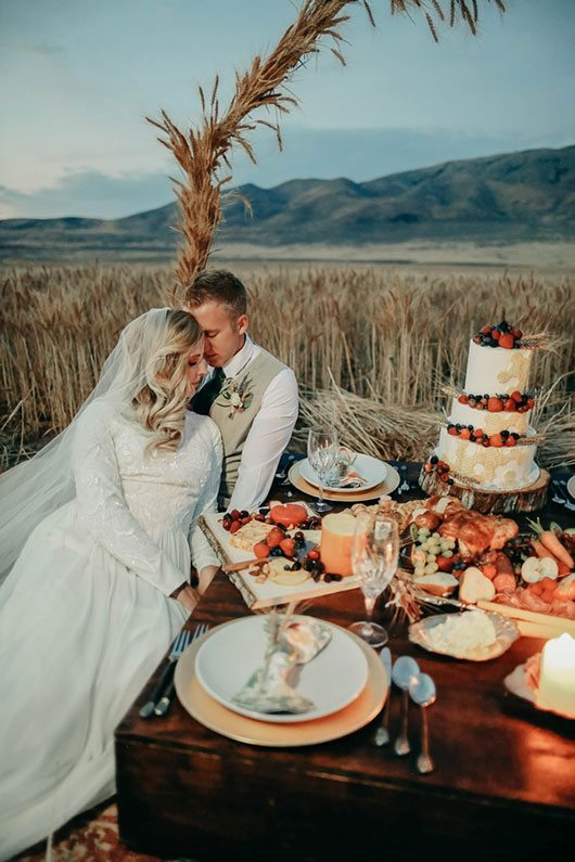 Bountiful Wheat Harvest Bride And Groom Sitting By Food
