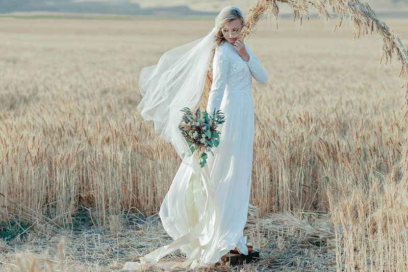 Bountiful Wheat Harvest Bride Holding Flowers In The Wind