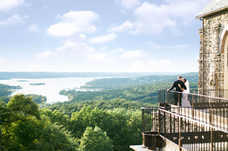Escape To Connect Amongst Nature At Big Cedar Lodge Bride And Groom Kissing On Balcony Overlooking Nature